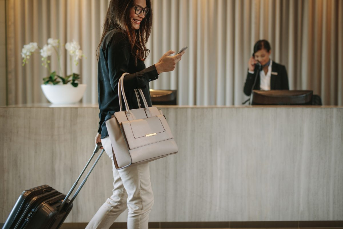 Woman,Using,Mobile,Phone,And,Pulling,Her,Suitcase,In,A